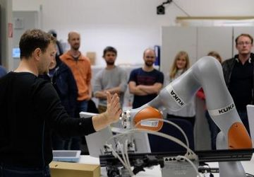 Man holds his hand to the robot